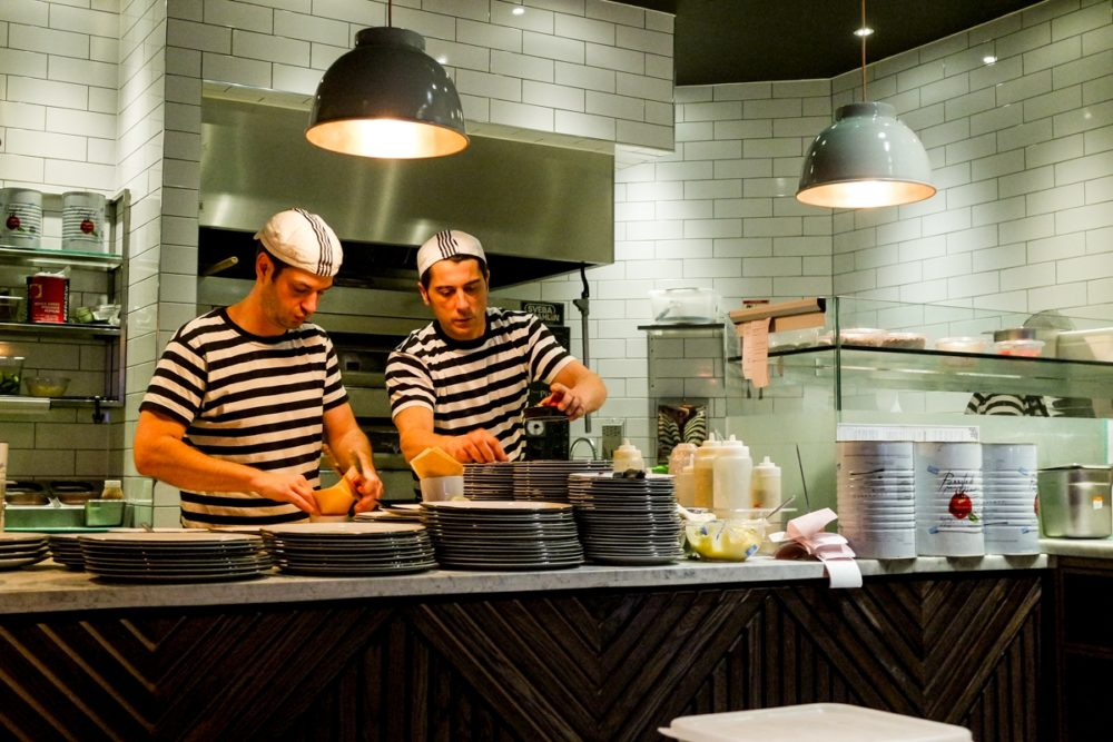 Two chefs working in the kitchen at Pizza Express