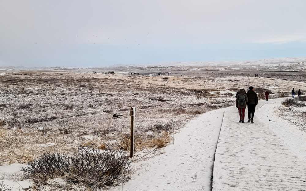 Couple walking in the snow to Gulfoss Waterfall | Pictures of Iceland in Winter #iceland #winterphotography #europe #nordiccountries #kinfolk
