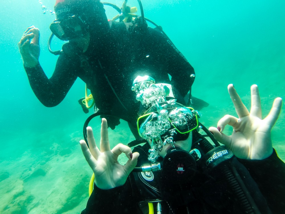Girl doing the OK sign underwater while scuba diving
