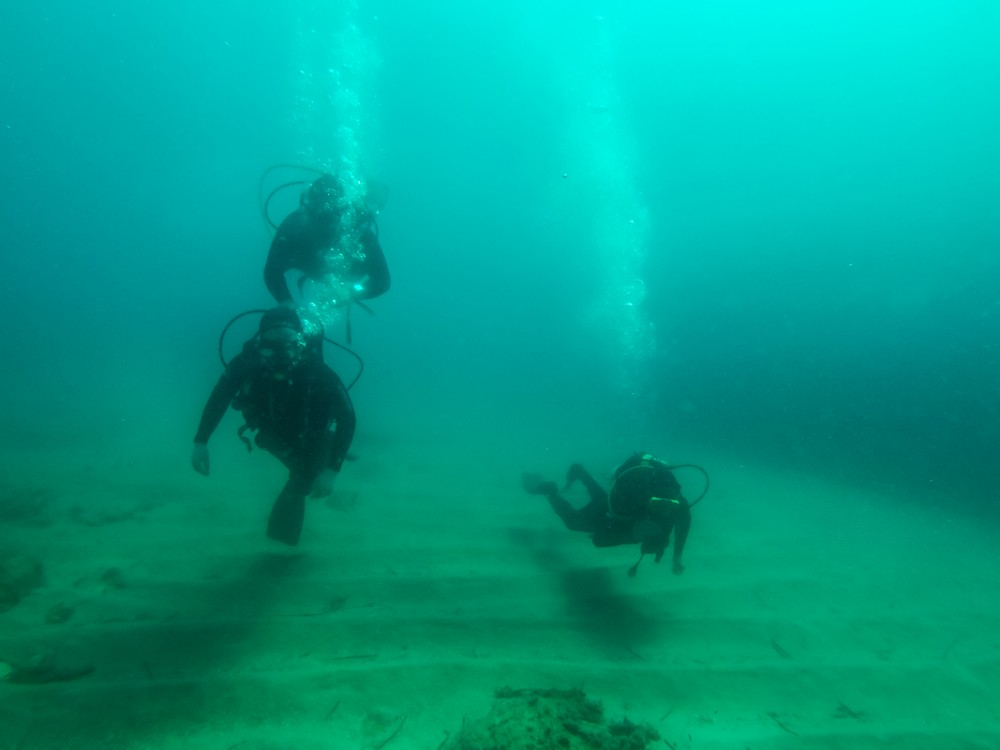 A group of three people scuba diving in Budva, Montenegro