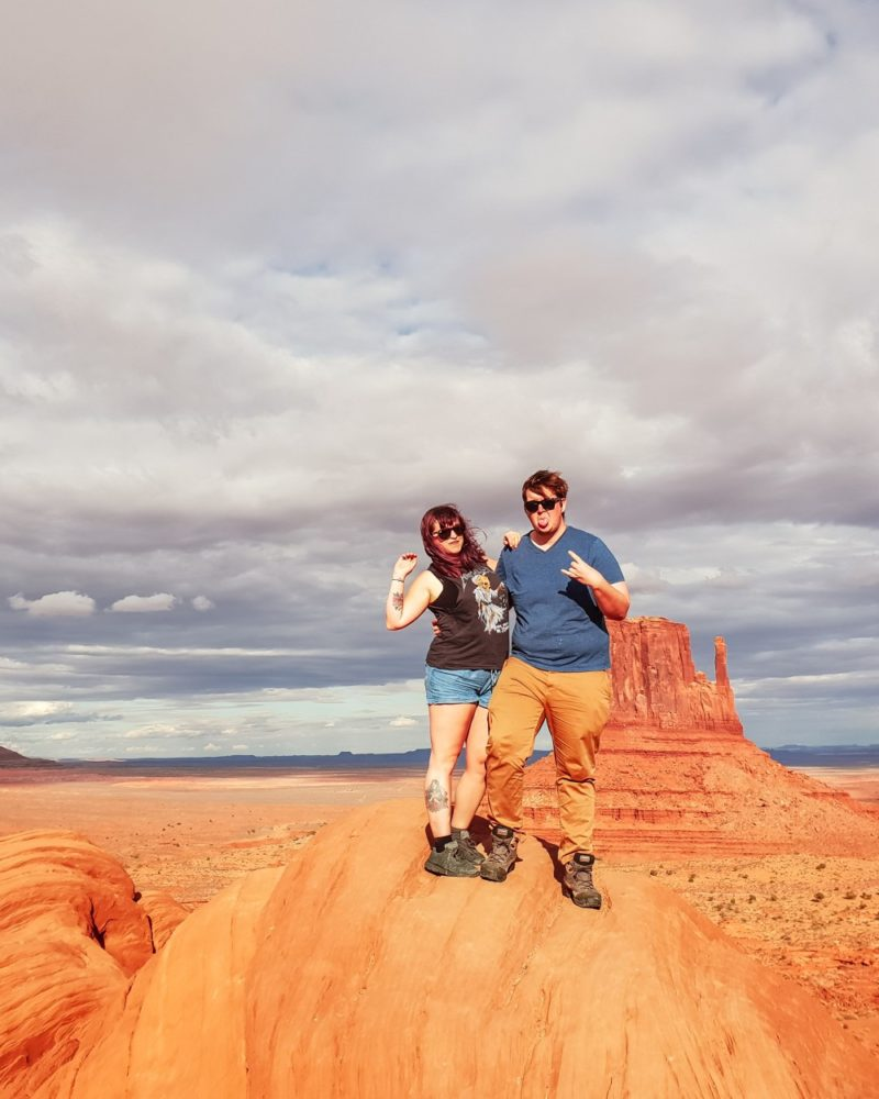 Couple at Monument Valley with view in the background | What to do at Monument Valley #monumentvalley #navajo #travelblog #utah #usatravel