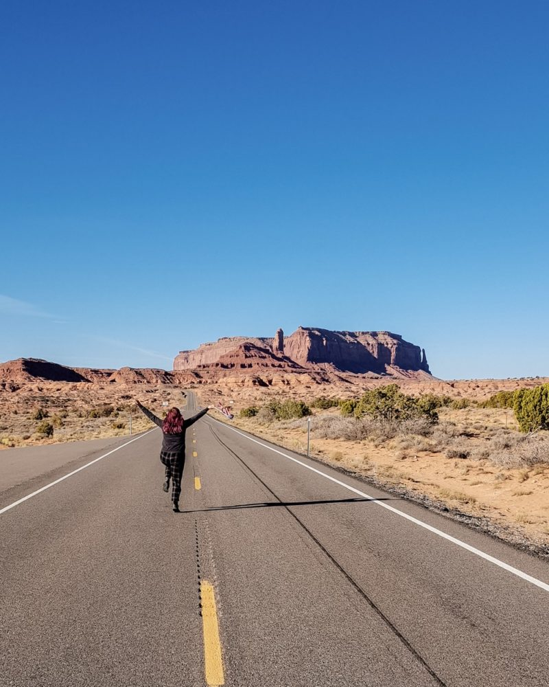 Girl running at Forrest Gump point, Monument Valley, Utah