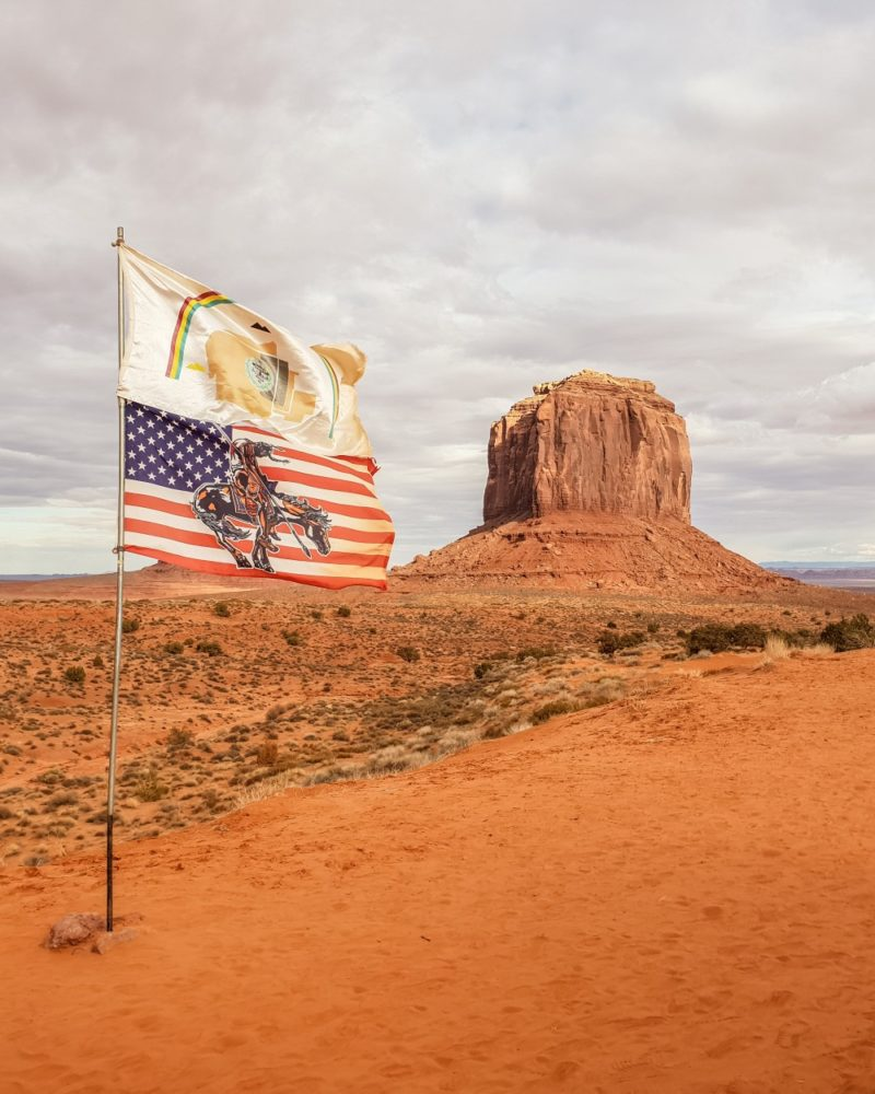 Flag at Monument Valley with butte in background | What to do at Monument Valley #monumentvalley #navajo #travelblog #utah #usatravel