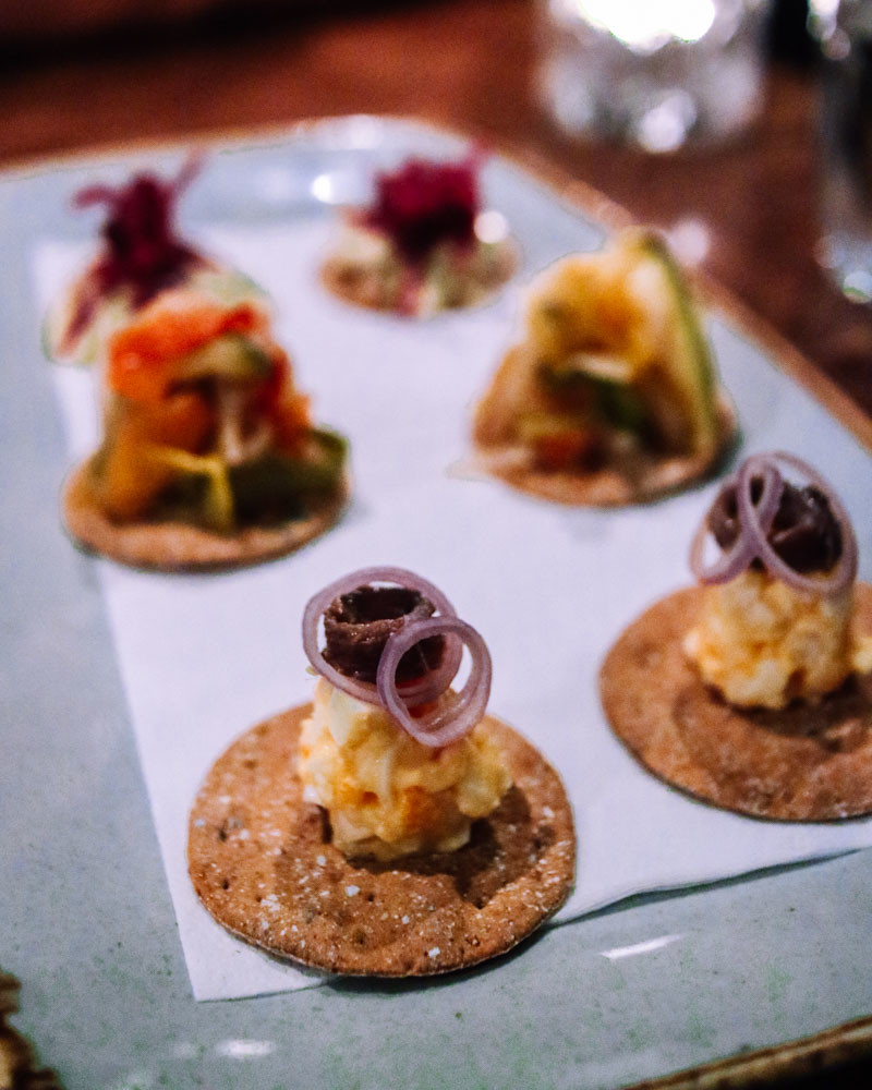 Egg and anchovy canape on a plate with other canapes in background