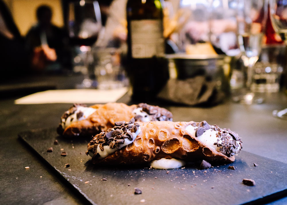 Two cannoli desserts on a serving board in restaurant