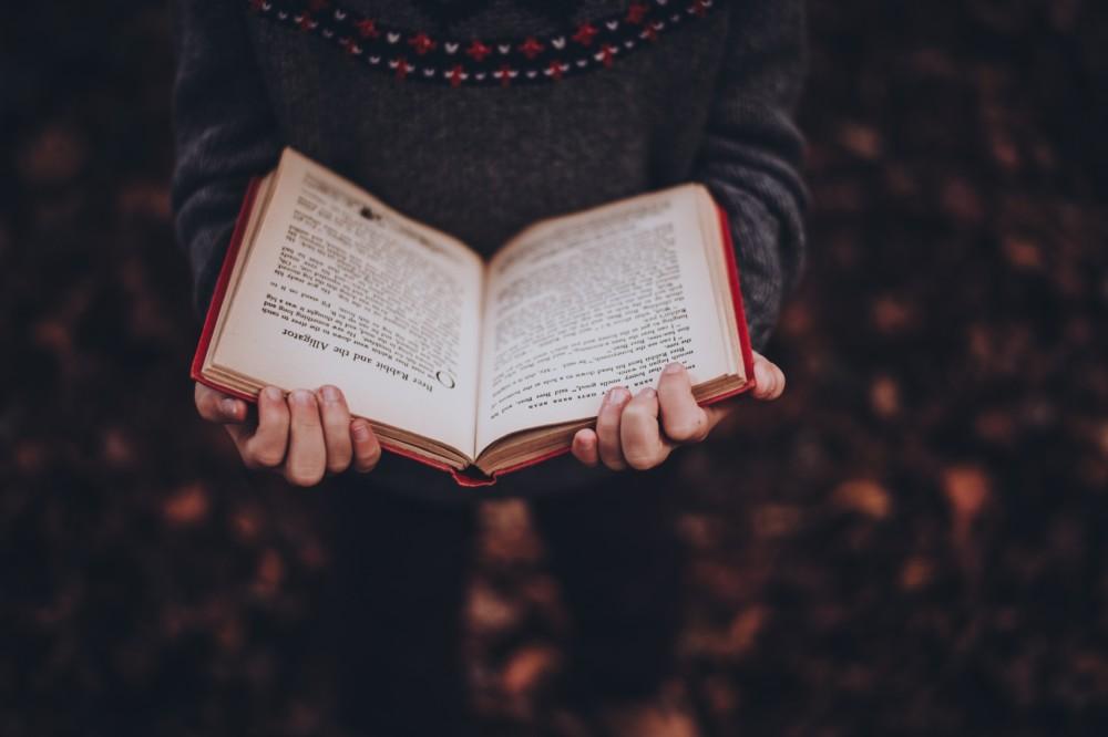 Moody image of book in girl's hands in autumn