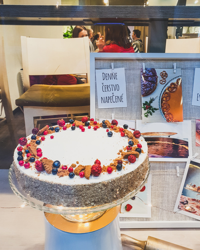 White iced cheesecake with berries in window display