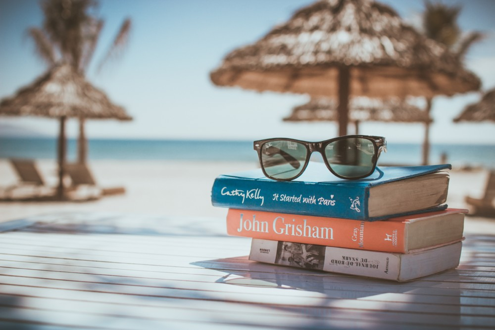 Stack of books with sunglasses on top on a beach table
