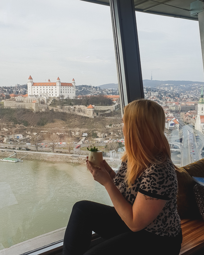 Girl drinking cocktail with view of castle