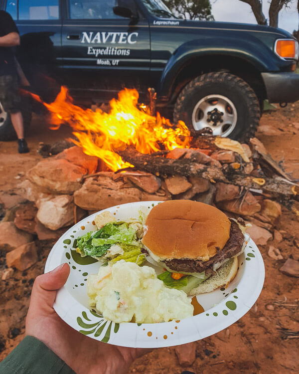 Plate with a burger, potato salad and lettuce, in front of a campfire